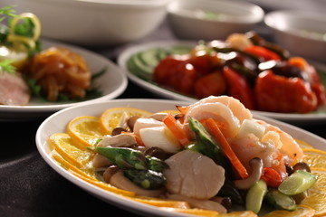 Sauteed scallops with lemon, mushroom and carrot on white dish
