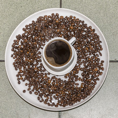 Coffee cup and coffee beans, top view
