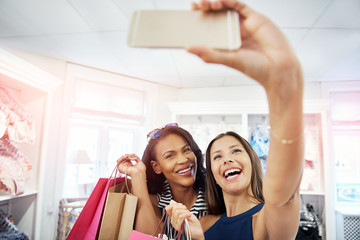 Laughing vivacious young women posing for a selfie