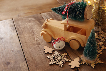 Wooden car carrying a christmas tree on wooden floor
