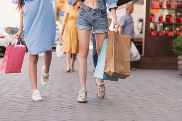 stylish women walking on the street with purchases
