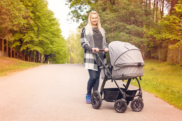young happy mother with baby carriage on beautiful autumn day