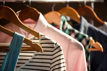 Trendy clothing on wooden hangers