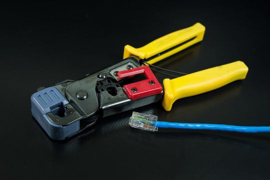Crimping tool for twisted pair on black background.