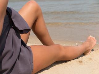 Beautiful tan female legs on sea beach holidays summertime