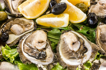 Oyster with lemon and olives