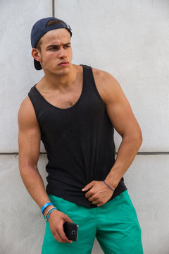 Young, caucasian, strong and handsome man wearing a black tank top and a cap. He has the smart phone in his hand. He looks with a seductive face while resting his arm on the wall.