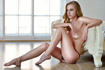 Beautiful sexy lady in elegant black panties. Fashion portrait of model indoors. Beauty blonde woman with attractive body in lace lingerie. Female ass in underwear. Naked girl