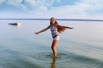 Piękna dziewczynka tańczy w wodzie jeziora.