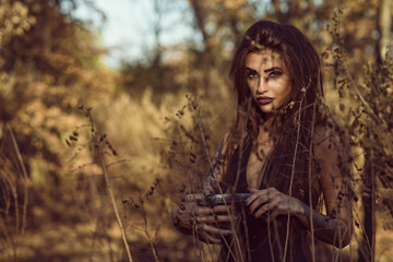 Portrait of charming dangerous young witch holding a pot with magic potion in the woods and looking straight with penetrating gaze. Halloween concept. Outdoor shot. Copy-space