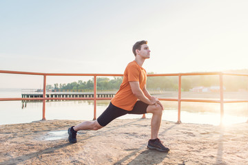 Young fit man stretching legs outdoors doing forward lunge.