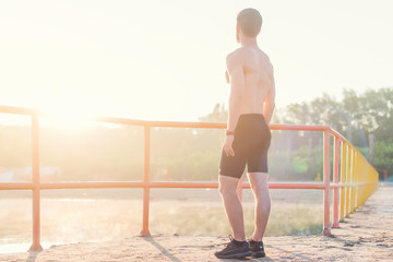 Young athlete man is looking out at sunset.