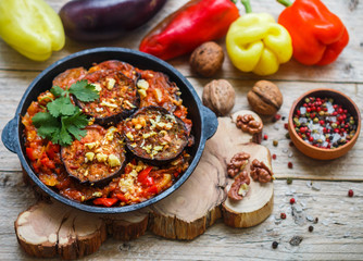 Baked eggplant with peppers, garlic, tomatoes and walnuts. Cold or hot appetizer. A rustic style. Selective focus