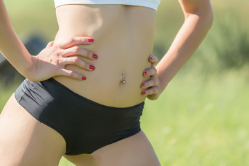 athletic woman in black shorts and piercings