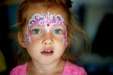 Pretty exciting blue-eyed girl of 2 years with a pink face painting
