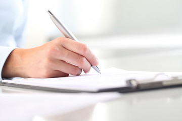 Woman's hands writing on sheet of paper in a clipboard and a pen