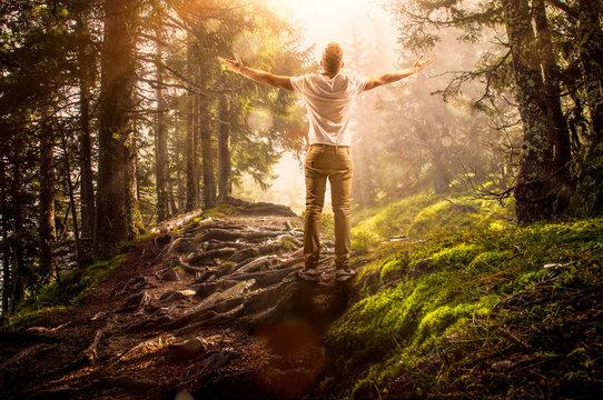 Mann steht im Wald und genießt die Sonne