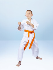 Boy karateka stands in the rack karate
