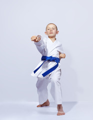 Karateka boy beats punch arm on a light background