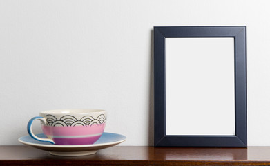 Blank photo frame with pastel tea cup white background