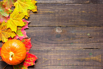autumn pumpkin with leaves on wooden background