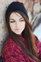Young beautiful long-haired brunette girl in a black hat with downcast eyes at  brick wall, close-up.