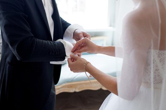 The bride helps her fiance to fasten cufflinks. Wedding worries