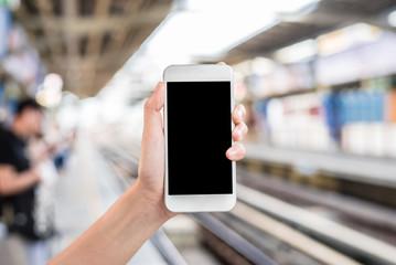 Hand holding mobile phone at railway platform station