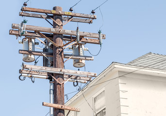 Residential wooden power pole with transformers and high voltage lines