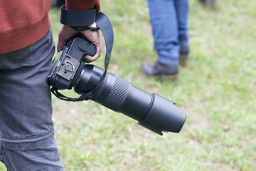 Man following another person, next to him/her, holding a dslr camera. Outdoors, on green lawn.