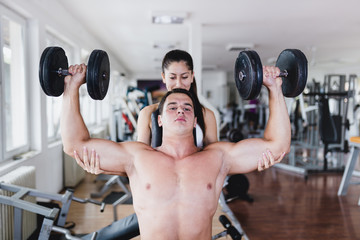 A man and a woman practicing together in the gym. Woman helping man in lifting weights.