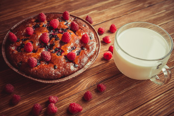 Fruit cake and cup of milk on the table.