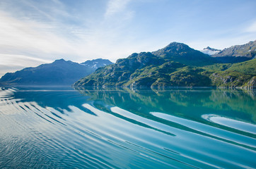 Cruise ship sailing in Southeast Alaska creates ripples across the calm waters of the Glacier Bay National Park and Preserve.