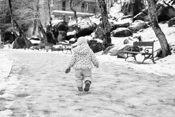 The little girl is in the park in winter