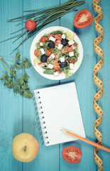 Vintage photo, Greek salad with vegetables, centimeter and notepad for notes, healthy food and slimming concept