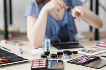 Colorful cosmetics on stylist workplace. Visagiste trying brush on hand. Stylish ladies lifestyle accessories. Variety of makeup tools, palettes and brushes.