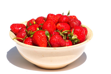 Raw strawberries lying in plate isolated on white background.
