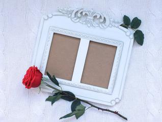 Винтажная фоторамка и красная роза на белом вязаном фоне.