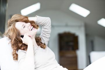 Frau sitzt auf dem Stuhl und telefoniert