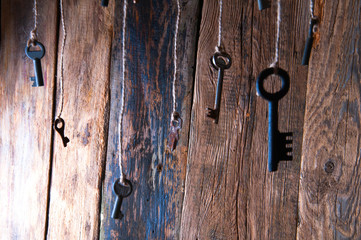Many keys hanging on a string. Wooden background. Selective focus