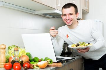 Successful man tasting vegetables dish near laptop