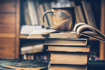 Cup with hot beverage and steam on a stack of books in the library, side view
