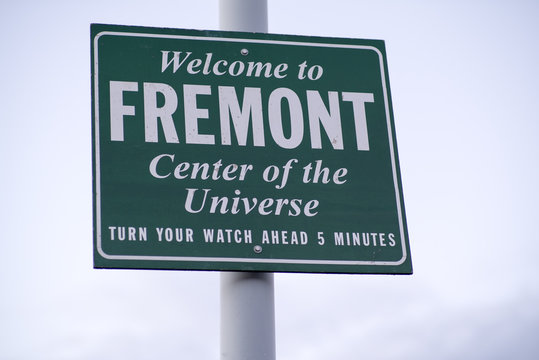 Welcome to Fremont - Center of the Universe - Turn Your Watch Ahead 5 Minutes Green and White Traffic Sign at the Entrance to the Fremont Neighborhood of Seattle, Washington, USA