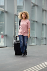 African american female walking with suitcase and backpack