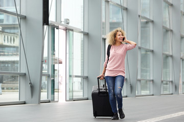 Happy young woman walking with suitcase and cell phone