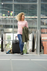 Smiling woman with luggage by escalator