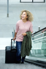 Smiling young woman standing on escalator with suitcase