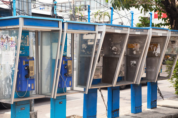 Row of old dirty payphones on a street in Thailand. Group of blue messy telephone booths in a city