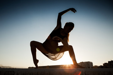 Dancer posing with the sun in the background.