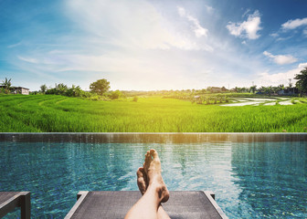 A guy relaxing on sunbathing bed at rice field in countryside area in sunrise morning